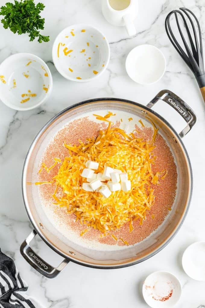 whisk together the heavy cream, paprika, mustard powder, and cheeses