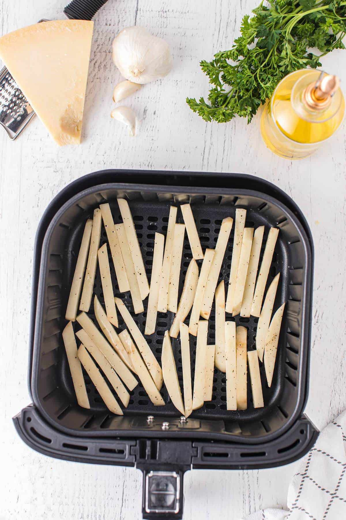 uncooked fries placed in the air fryer basket
