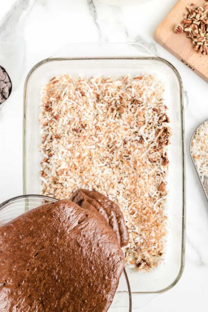 Pour the cake mix over the top of coconuts and pecans layer