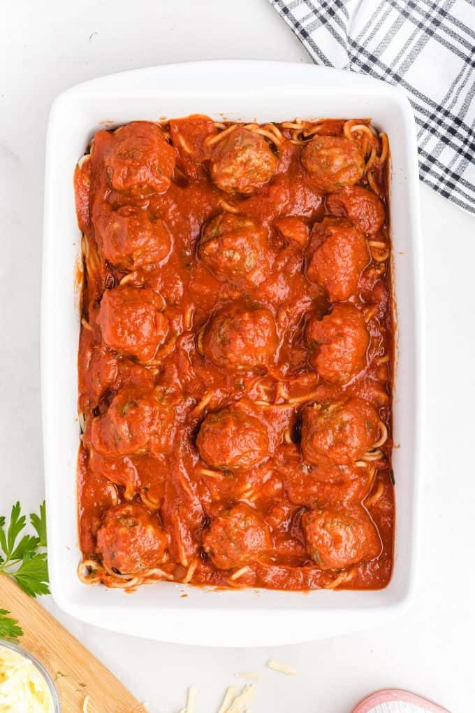 pouring pasta sauce on top of the casserole