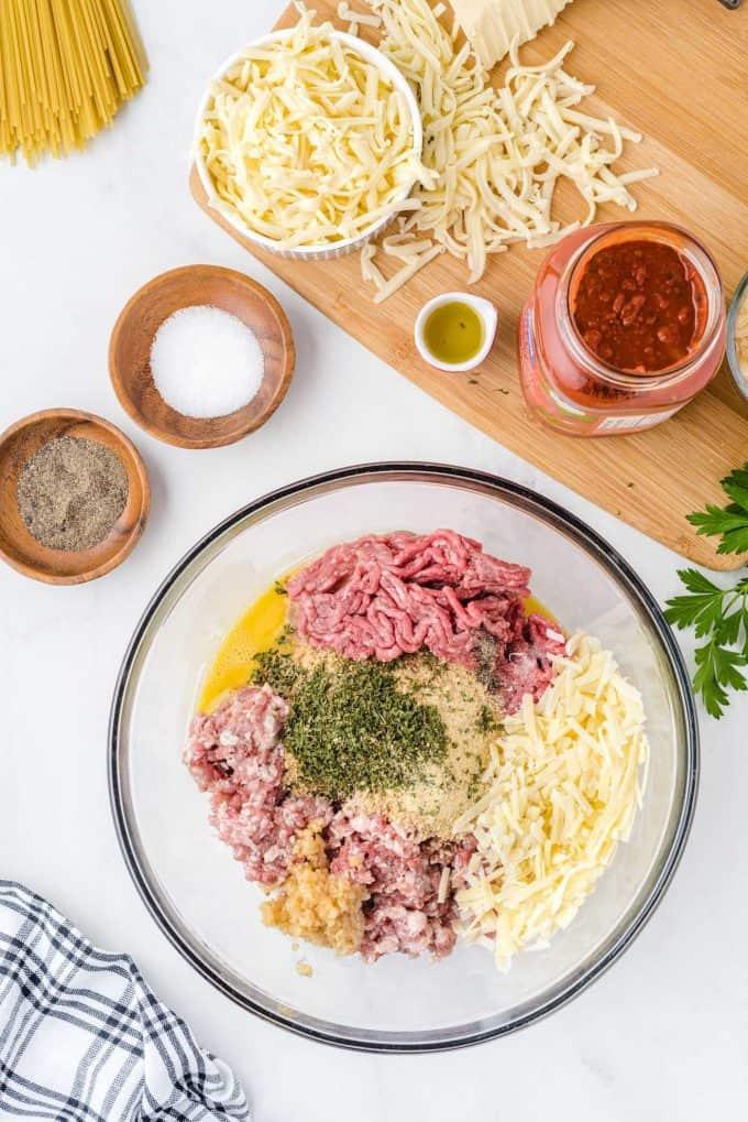combine ground beef, ground pork, Italian breadcrumbs, whole milk, minced garlic, Italian seasonings, onion powder, dried parsley, Parmesan cheese, salt, pepper, and lightly beaten eggs in large mixing bowl