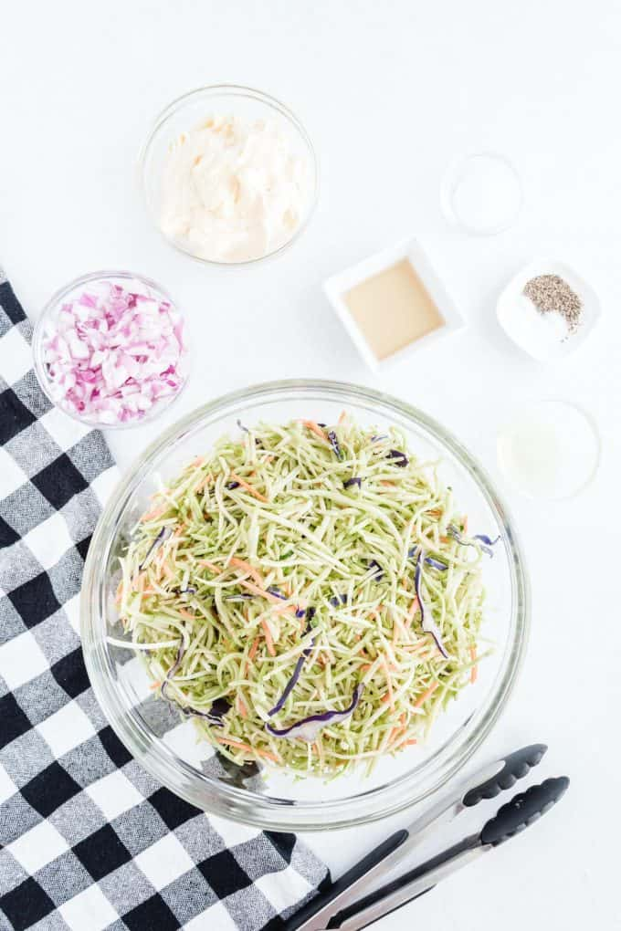 broccoli slaw in big mixing bowl with other ingredients around it