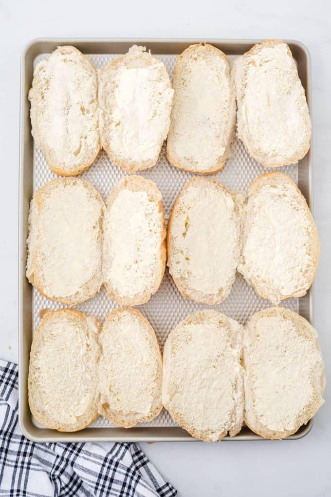 butter on hoagie buns on top of baking sheet