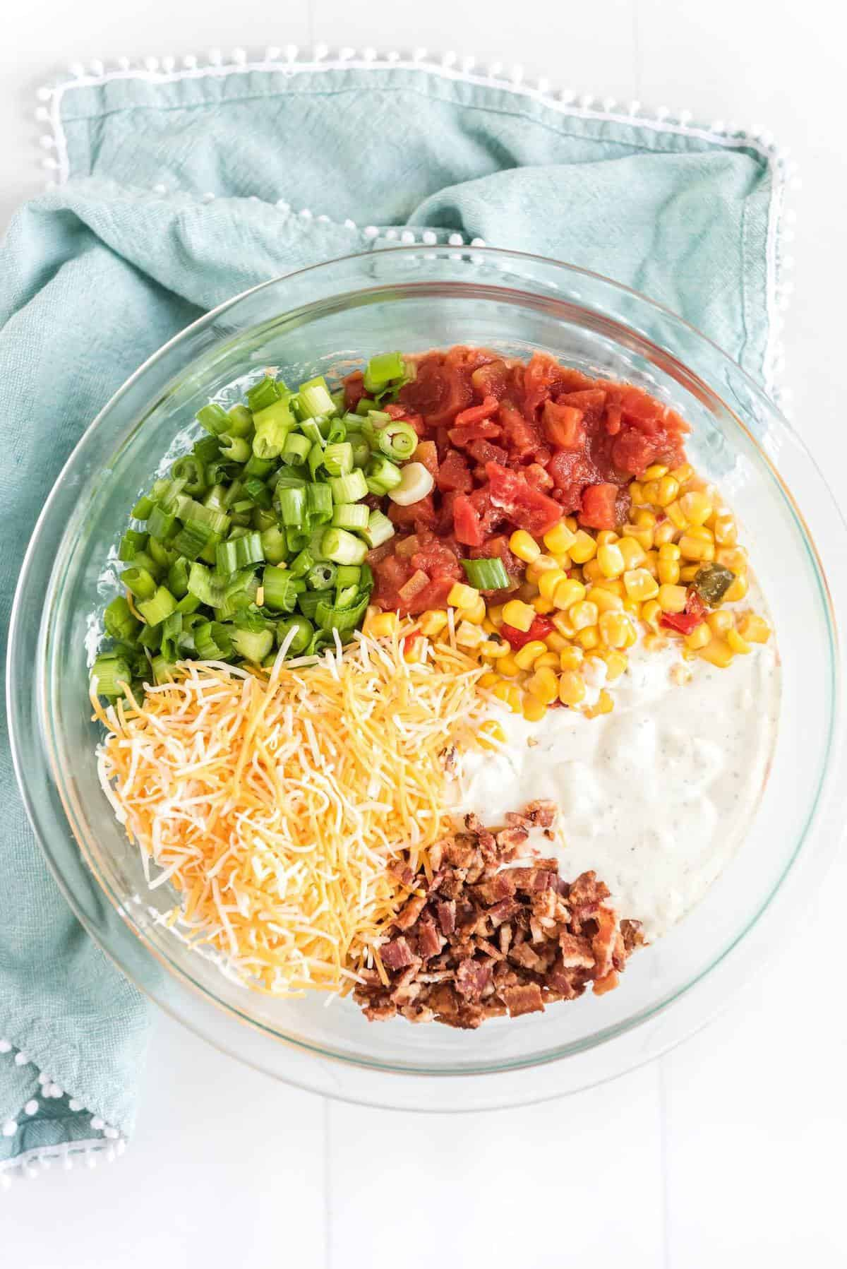 add in shredded Mexican cheese, chopped green onions, Roten, corn and bacon