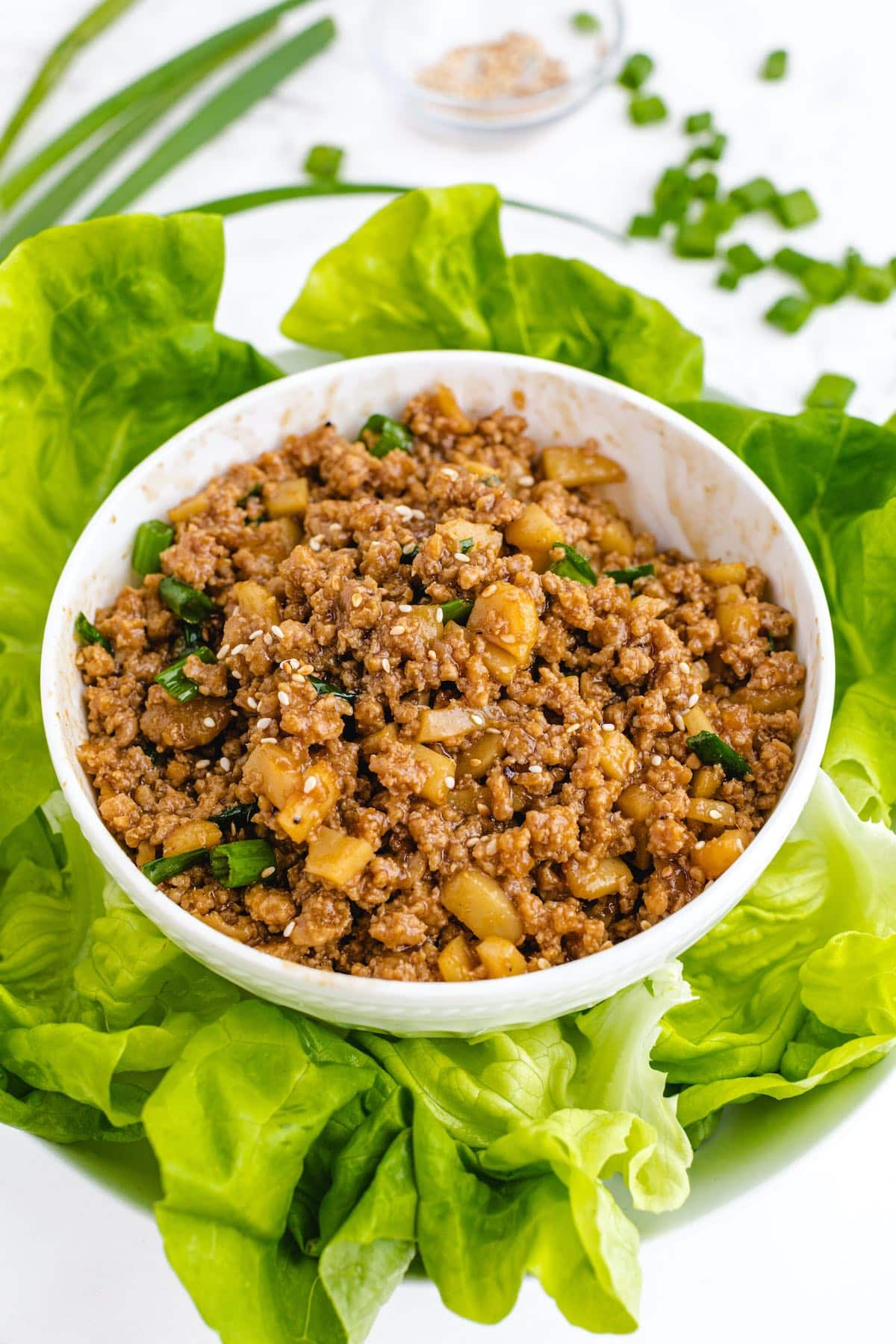 saute chicken in a bowl surrounded by lettuce leaves