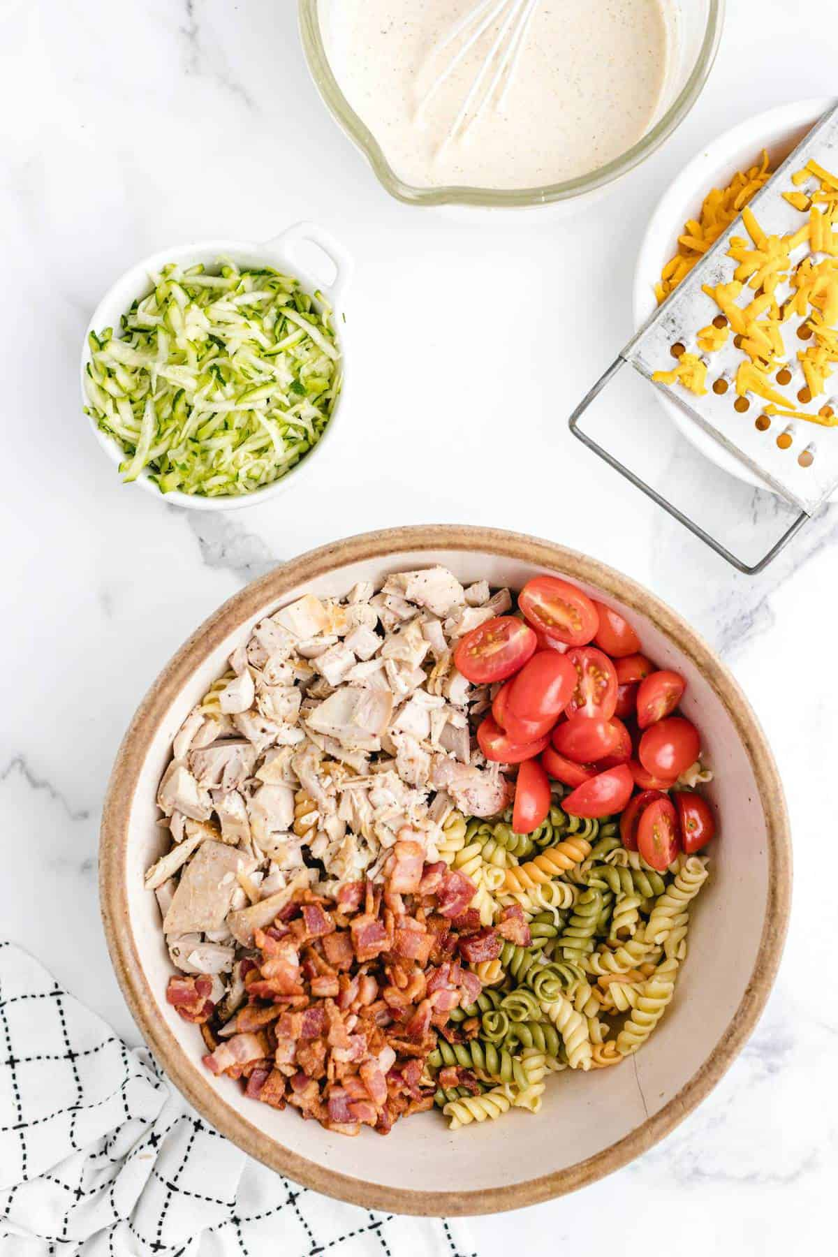 Add chicken, pasta, tomatoes, cooked bacon in a large bowl