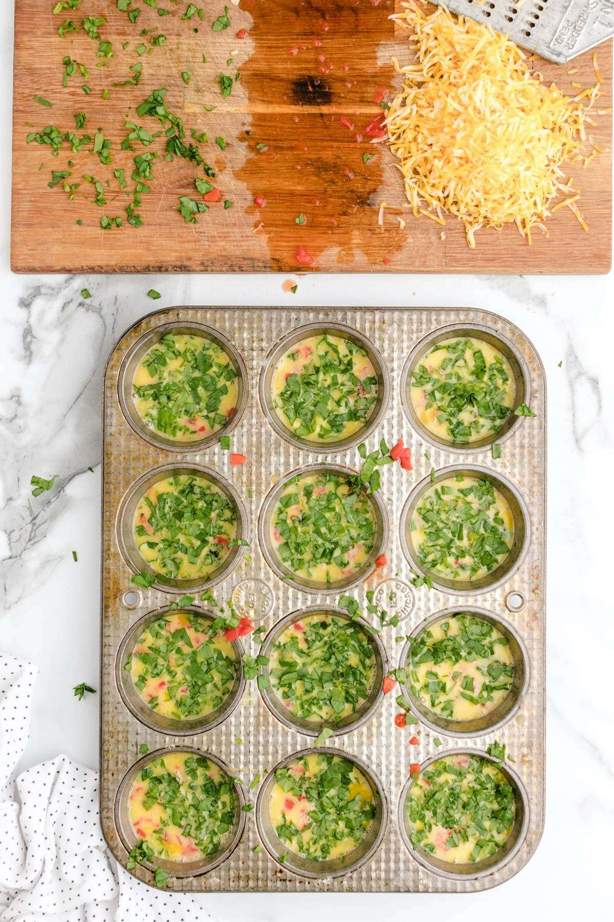 add spinach to each muffin spots