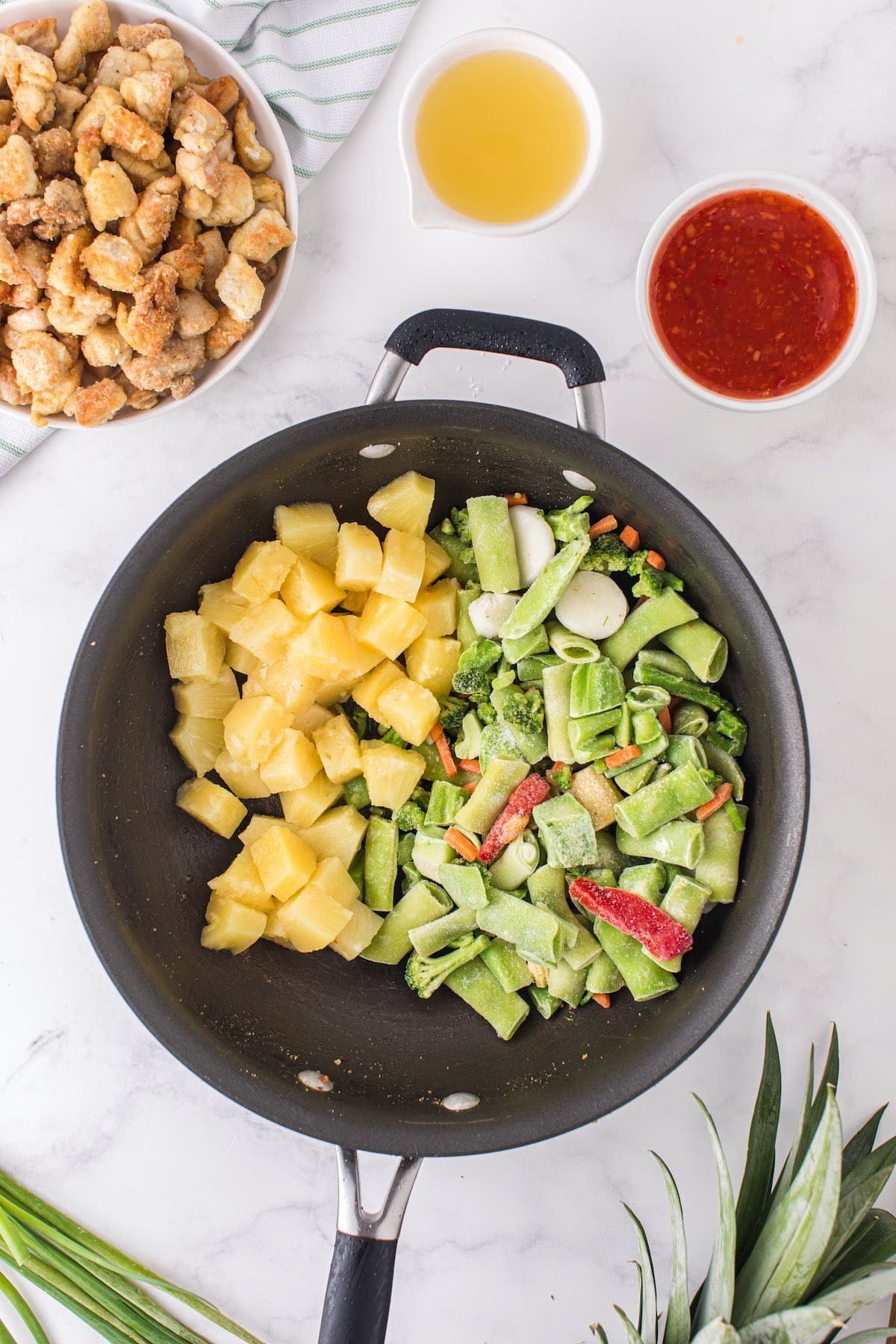 avocado oil, frozen vegetables, and pineapple in the pan