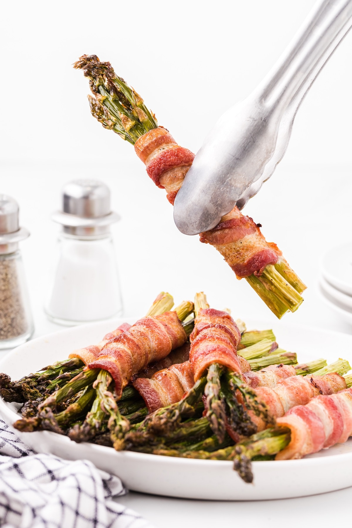 bacon wrapped asparagus picked up with tong