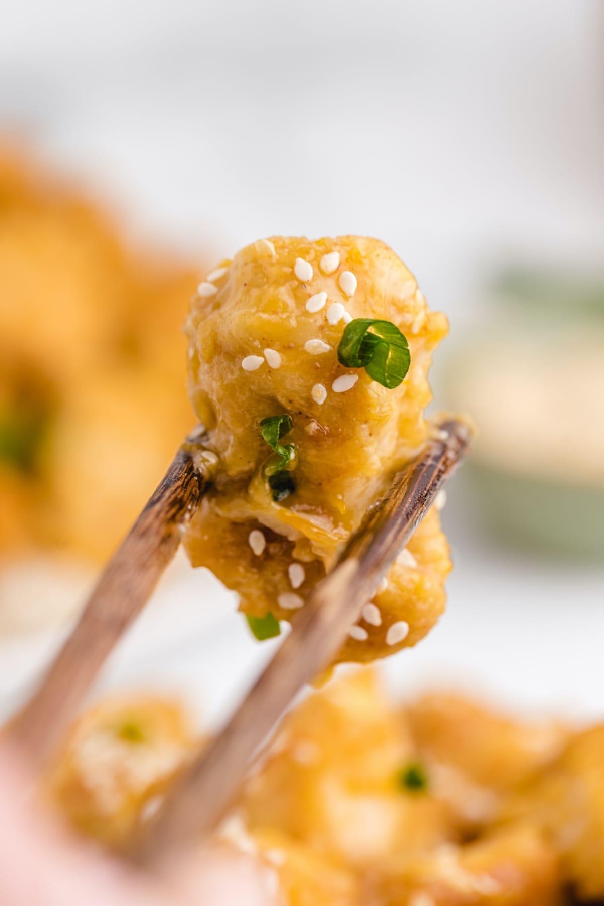 orange chicken held in chopstick