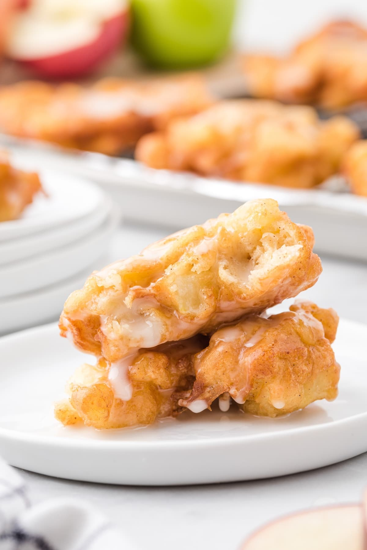 apple fritters stacked on a plate