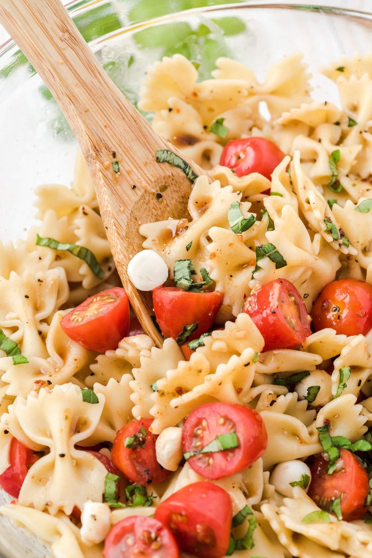 mixing caprese pasta salad in a bowl