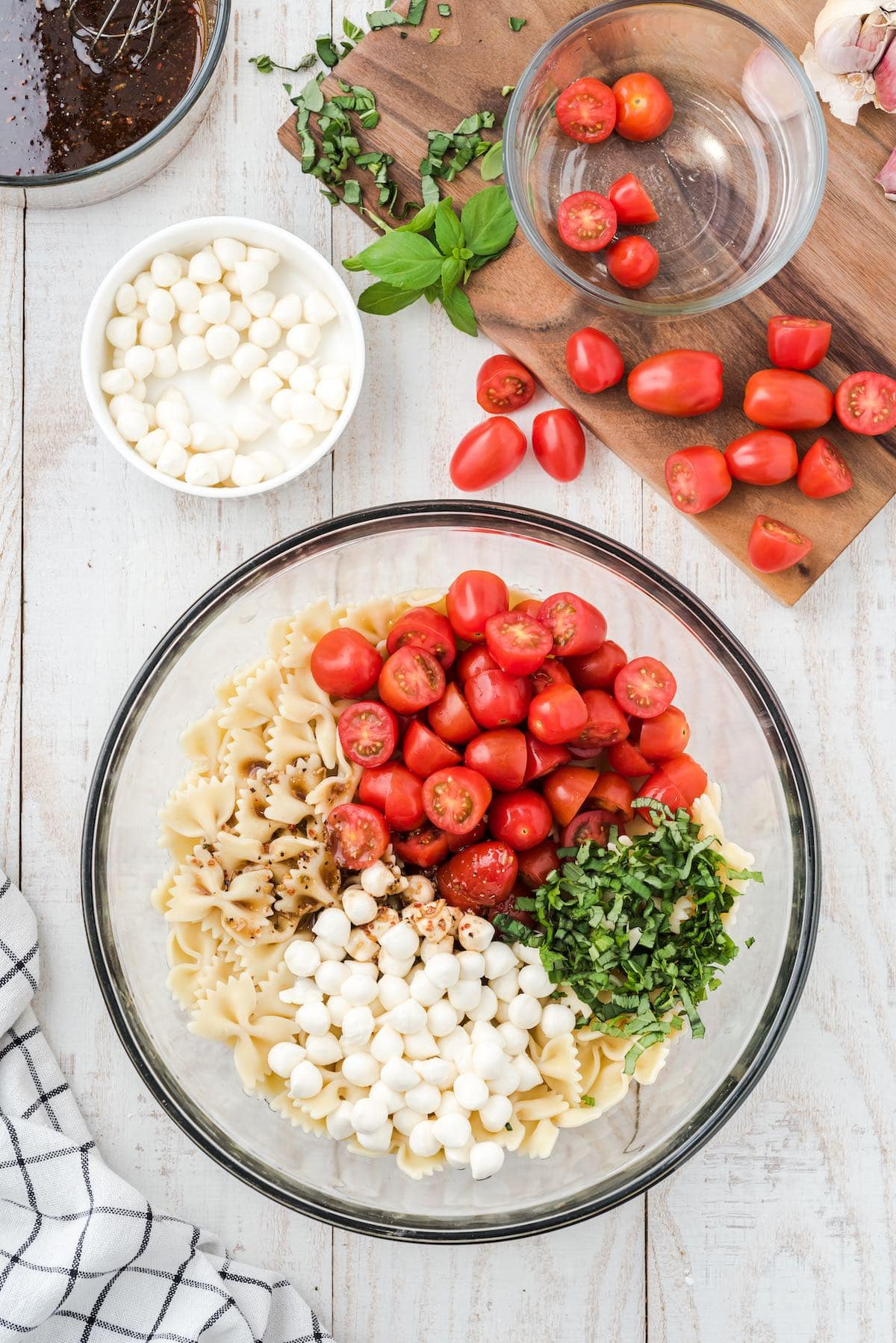pasta mixed with halved grape tomatoes, mozzarella pearls, fresh chopped basil in a bowl
