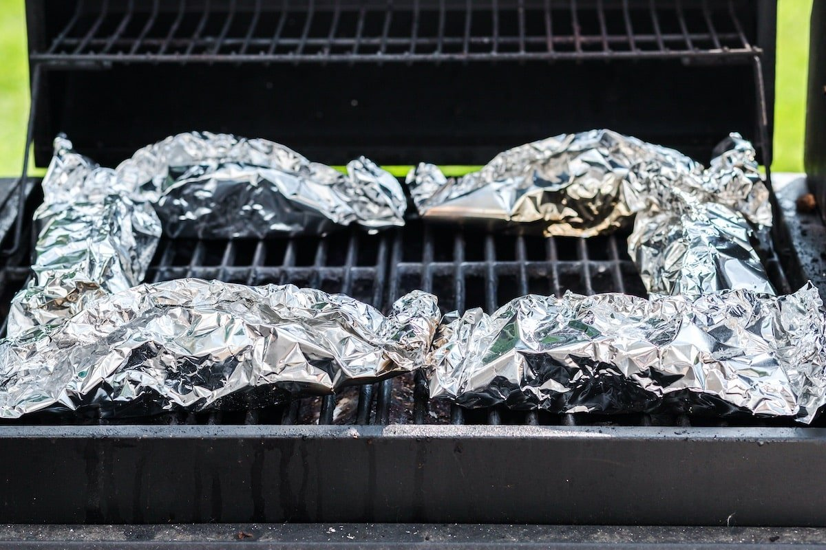 place the foil packets around the edges of the preheated grill