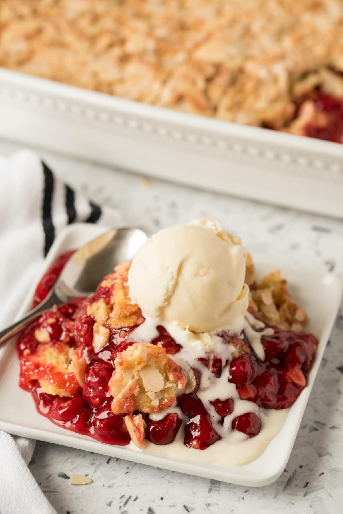 cherry dump cake on a plate served with ice cream