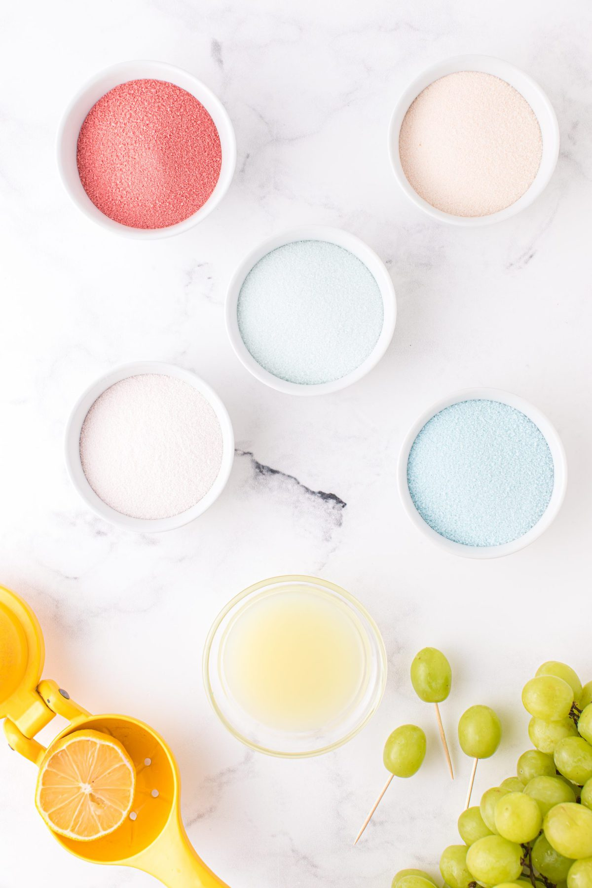 lemon juice in 1 bowl and 3 separate bowls with coloured gelatin powder