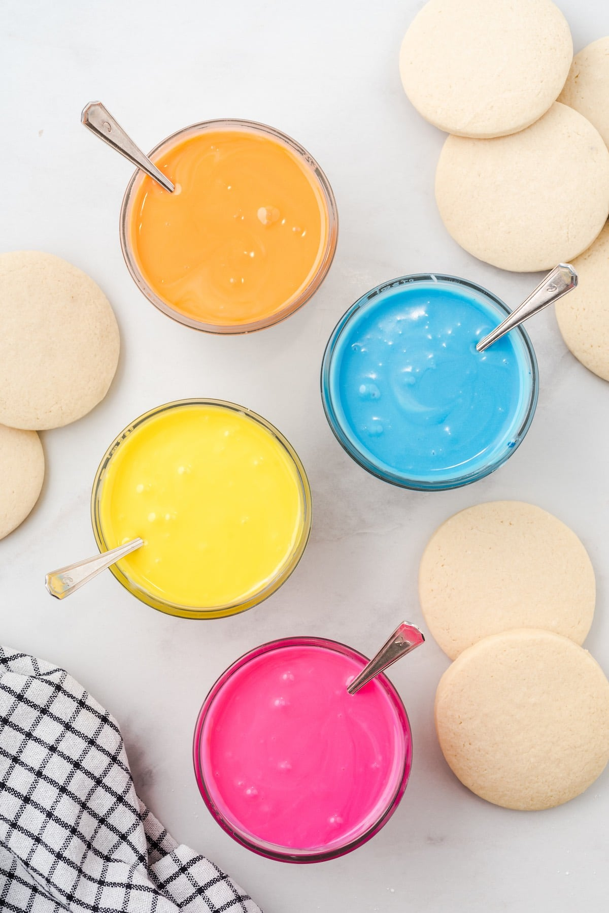 sugar cookie icing in 4 separate bowl, orange, yellow, blue and red