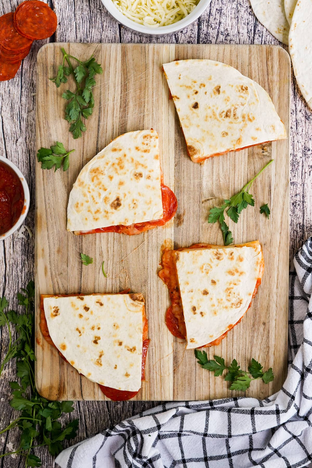 Pizza Quesadillas on top of wood chopping board