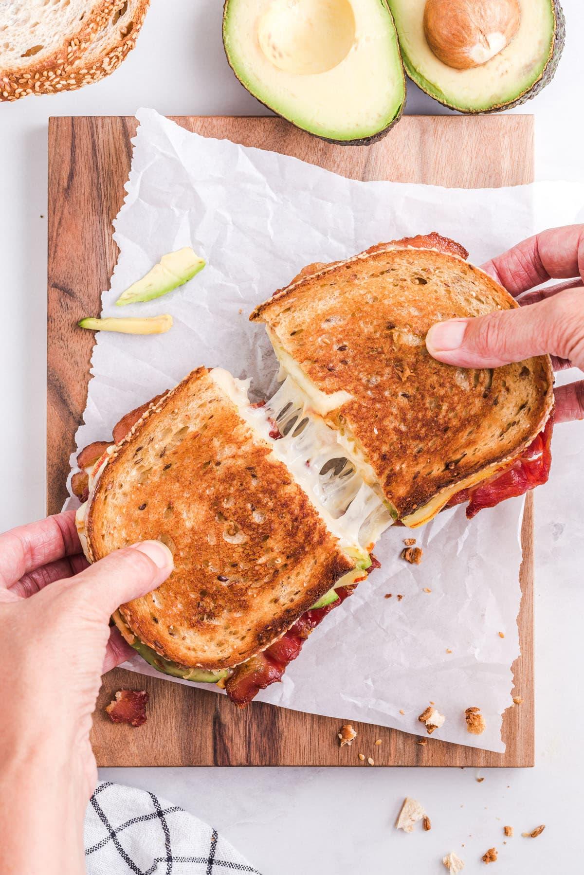 hand splitting the bacon avocado sandwich in half
