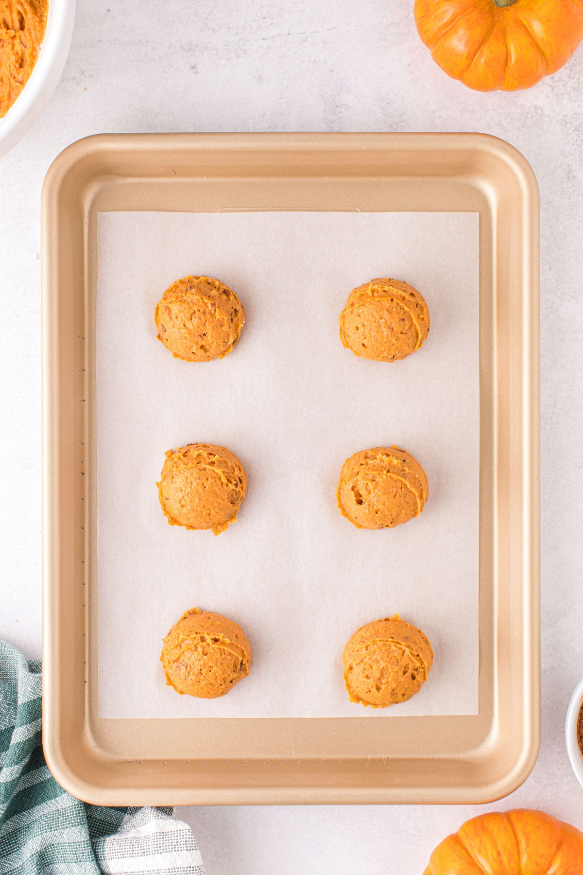 Drop scoops of cookie dough onto the parchment-lined sheet pan